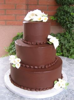 Cake, No flowers. Plain chocolate cake base. Decorations and design will be customized.