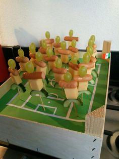 Voetbalveld met voetballers van kaas, mini knakworstje, komkommer en druif...