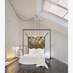 stunning bed on castors, herringbone floors, exposed bulbs and white, white, white.  incredible loft bedroom.