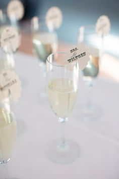 Table numbers and names with escort cards on toasting glasses ....this is cute, simple and elegant!
