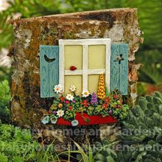 This window is from the Merriment Fairy Garden Collection designed by Mary Engelbreit.  It has a red windowbox filled with colorful flowers.