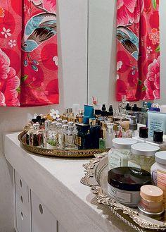 Bandejas marroquinas exibem perfumes e cremes no banheiro da estilista Adriana Barra