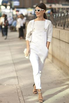 White overalls paired with a knit sweater and heels.