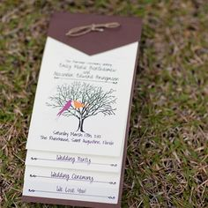 The program booklets that had information about the ceremony and bridal party. They featured the couple's wedding logo of two love birds in a tree.