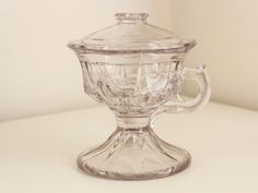 """An antique glass oil lamp in great condition, this petite light has a finger hook for portability. it is in suitable condition for collecting and is rare in this form—all available examples are larger, have metal collars, and lack finger hooks.  Details: 6"""" high by 4.8"""" in diameter, 5.5 wide at handle. Circa 1880-1900. Very good condition with no glass flaws found and only very minor purpling and wear to underside of base consistent with age. Please note that it has not lost its collar, it…"""