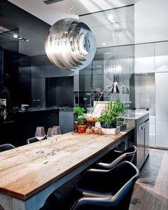 Cocina dividida por cristales tintados . Lampara de Foscarini , mesa antigua y sillas Tulip