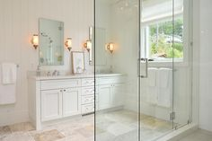 White+cottage+bathroom+features+walls+clad+in+vertical+shiplap+lined+with+a+white+dual+vanity+...