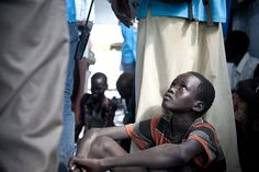 Duol, 14, the eldest of Biel's five orphaned nephews, watches UN staff at work in Pugnido refugee camp. UNHCR/Catianne Tijerina