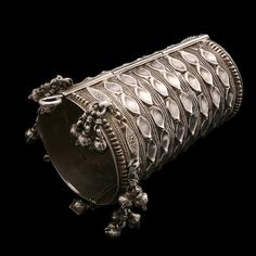 Silver Wedding Cuff  ~  Himachal-Pradesh, India  ~  Circa Early 20th Century  ~  Handmade (as one of a pair) for the daughter of a wealthy Himachali family, it was a traditional bridal accessory for brides in the Himalayan Gaddi tribe. It displays devoted craftsmanship in the details - from the painstakingly curved pattern to the charms attached to the rim.