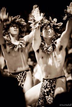Kane (men) dancing hula kahiko (ancient hula), wearing ti leaf leis on heads and necks and malo (Hawaiian loincloth). Photo by Kai Markell of Honolulu, Hawai'i.