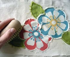 Raw edge applique: 'Spray the appliqués with water, then gently brush the edges to fray. When I'm done, I like to throw it in the dryer for a few minutes then trim off the really long scraggly bits.'