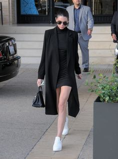 Kendall Jenner wears a black mini dress, black duster coat, and white slip-on sneakers at Barney's New York on Dec. 2015 in Los Angeles, CA. Kendall Jenner Dress, Kendall Jenner Modeling, Kendall Jenner Photos, Kendall Jenner Outfits, How To Wear Sneakers, Dress With Sneakers, White Sneakers, Maxi Coat, Pulls