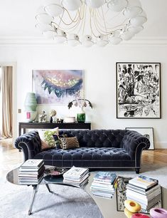 Contemporary living space with a large chandelier, and a blue tufted sofa