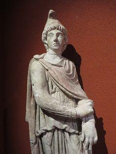 Cautopatés, Calcaire, fin IIe-début IIIe siècle, fouilles à Bordeaux, temple de Mithra. Compagnon de Mithra, Cautopatés est habillé à l'orientale avec un bonnet phrygien et une longue cape rouge. Avec sa torche baissée, il symbolise le crépuscule, l'automne et la mort, pendant de Cautès qui symbolise, lui, le renouveau. Musée d'Aquitaine