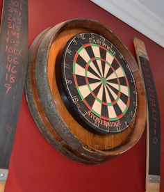 This dart board kit is mounted on a retired wine barrel. The kit comes with a high quality cork dart board and mounting hardware that makes installation a breeze. This piece is the perfect addition to any game room. The barrel heads have roughly a 23 Wine Barrel Diy, Wine Barrels, Barrel Bar, Barrel Table, Wine Cellar, Table Baril, Dark Stained Cabinets, Dart Board Cabinet, Dart Board Backboard