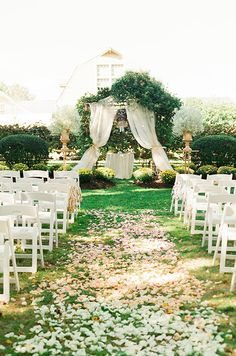 A stunning wedding aisle covered in flower petals leads to an altar draped in white cloth and flanked by oversized floral arrangements. Check out this romantic pink vineyard wedding.
