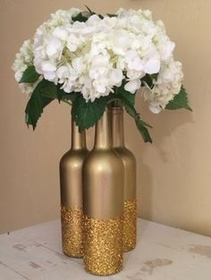 Either just the bottle or all over glitter (spray paint). Baby's breath and pearl votives around. Need ~60 Bottles (3 per table + extra)
