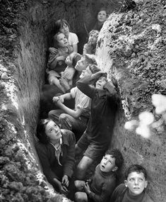 Children take refuge in a trench whilst watching a dogfight unfold in the skies above during the Battle of Britain C. 1940. [846x1024]