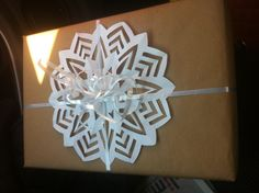 Present wrapped in brown paper with snowflake and ribbon!