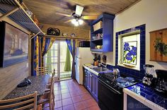 "Beautiful ""butler-pantry"" style kitchen  leads to the pool garden. Elegant blue tiles frame a stain glass orchid art piece in the window. Charming French-Caribbean style ambiance."