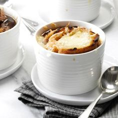 Classic French Onion Soup 5 tablespoons olive oil, divided  1 tablespoon butter  8 cups thinly sliced onions (about 3 pounds)  3 garlic cloves, minced  1/2 cup port wine  2 cartons (32 ounces each) beef broth  1/2 teaspoon pepper  1/4 teaspoon salt  24 slices French bread baguette (1/2 inch thick)  2 large garlic cloves, peeled and halved  3/4 cup shredded Gruyere or Swiss cheese