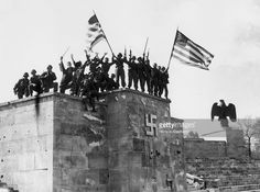 Men of the 45th division of the US 7th Army wave American flags from the dais of the Luitpold Arena in Nuremberg after capturing the city. It was in this very arena that the annual Nazi party rallies were held.