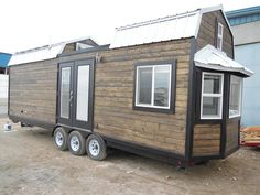 The 30' Barn Style tiny house has a unique roofline with a deck in the middle. On one end of the roof is a 10-panel 1000 watt solar kit for off-grid living.