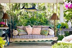 Contractor Tim Givens built the swinging daybed on the back porch of Liza Pulitzer Calhoun's Palm Beach house, and she simply covered its seat with a favorite tablecloth. The pillows are from Anthropologie and Roberta Roller Rabbit. The swordfish was found in an antiques shop.