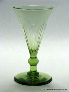Olive Green Wine Glass c1830 A rare colour, it has a trumpet bowl with slice cuts that extend down to a ball knop above a short plain stem. Plain foot with polished pontil.