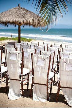 beach wedding ceremony white chairs