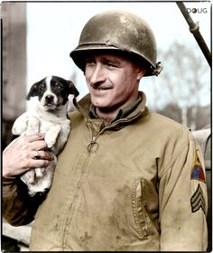 Sergeant James Simcox, US 4th Armored Division from South Bend, Indiana, , shows off a young puppy named 'Oscar' who had been given to Simcox's tank crew by a grateful French Civilian.  The photo was taken on the 16th of December 1944 at Fenetrange in France.