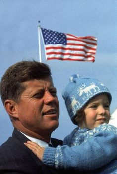 Democratic candidate John F. Kennedy holds 2-year-old daughter Caroline on Election Day, 1960.