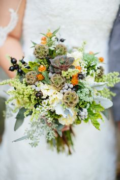Bridal bouquet by designer Katie Pollard of Color My World Flowers - Nashville, Tennessee, with succulents, scabiosa pods, orange gompherna,...