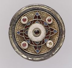 Disk Brooch, early 7th century, made in Faversham, England, gold sheet, garnets with patterned foil backings, blue glass. The region of Kent, in southeastern England, was an important center of Anglo-Saxon jewelry production of the type represented by this delicate, brightly colored piece. The interlace patterns created by gold filigree and the polished garnets reflect the high quality of goods worn by individuals in life and later buried with them.