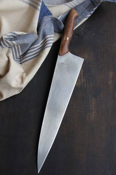 """This is a 9"""" chef with a handle made of wood from my family's apple orchard! I'm playing with photographs and trying to work out how to best capture the knives. It's tricky with the reflection on the steel and the handle wood often blending into the background, but it's a fun challenge!"""