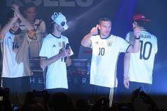 Die Nationalspieler Emre Can (l.) und Lukas Podolski (2.v.r.) präsentieren mit Rapper Cro (2.v.l.) in Berlin das neue Heimtrikot der DFB-Auswahl für die EM 2016 in Frankreich.
