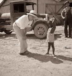 This is picture of a farm owner in Mississippi. He is chatting with one of the children of a worker on his farm. The picture was taken in 1937....