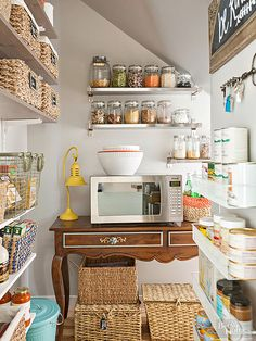 What the original pantry lacked in personality, it made up for in useful space. The storage space became a decorative extension of the kitchen by removing the door and adding shelves for baskets and jars. Clear glass containers save time when identifying contents and look pretty lined up in a row, while a console table serves as a handy spot for the microwave.
