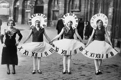 """  Three women wear clock costumes in the Place Vendrome in Paris. The local custom on St. Catherine's Day is for models and shopgirls, midinettes, to celebrate in honor of Catherine, their patron saint. Every year on December 2, Parisian shops close, and women like these will participate in a parade and dancing all night. 1932."""