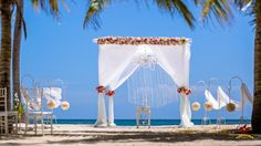Gorgeous white wedding arch with a live floral arrangement made with white and ivory roses and light pink and fuchsia roses. The arch is also adorned with a crystal chandelier  and crystal curtain beading. #weddings #caribbean #weddingagency #destinationwedding #dominicanrepublic #caribbeanweddingagency