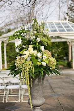 ~~ large urns flank the aisle. Arrangements a stunning mixture of antique green hydrangea, Bells of Ireland, 'Green Trick' dianthus, green hanging amaranthus, Queen Anne's lace, parrot tulips, white snap dragons, dusty miller & greenery   Dorothy McDaniel's Flower Market; Ann Wade Parrish Photography