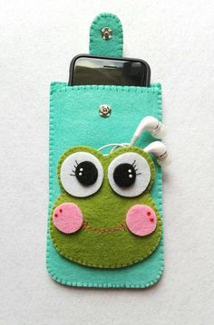 I wanted to create this case to be able to always carry with you cell phone and earphones . the case is made of felt green water and a nice frog / pocket is applied to the headphones . the closure is with clip and a lovely white wooden butterfly comple Felt Crafts Patterns, Felt Crafts Diy, Felt Diy, Sewing Crafts, Sewing Projects, Felt Phone Cases, Diy Phone Case, Pochette Portable, Cell Phone Holder