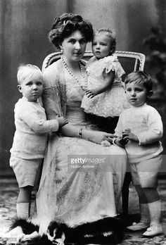 Queen Victoria Eugenie of Spain (1887 - 1969), wife of King Alfonso XIII of Spain, whom she married in 1906, with her children. From left, Prince Alfonso (1907 - 1938), Princess Beatrice (1909 - 2002), and Prince Jaime (1908 - 1975).