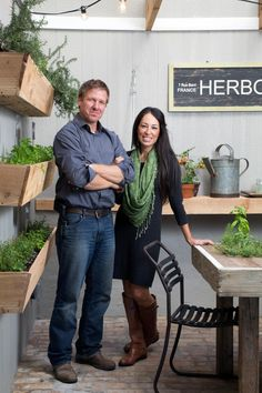 Joanna and Chip Gaines pose in a greenhouse for a portrait photo.
