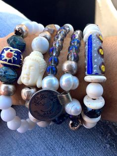 This Boho chic bracelet stack is a set of 4 bracelets handcrafted with African trade beads, old African silver beads, Czech beads, white and cream agate, freshwater pearls and glass beads. They are accented with a Buddha and Afghan coin. 7 if you need different sizing leave me a message with your order indicating your wrist measurement.    1 double wrap bracelet with glass beads, pearls, African silver beads, Afghan coin 1 cream magnesite bracelet with African silver beads, Czech beads and a…