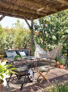 shady outdoor living space with hammock and thatched patio roof