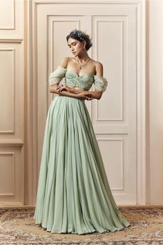 Sage-green lehenga in georgette with a matching off the shoulder top with thread, silver poth (small beads), sequin, and silver salli (pipes) embroidery on net with organza draped sleeves Indian Fashion Dresses, Indian Gowns Dresses, Dress Indian Style, Indian Designer Outfits, Ball Dresses, Designer Dresses, Indian Outfits Modern, Indian Wedding Wear, Indian Bridal Outfits