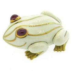 18k gold David Webb frog brooch, decorated with white enamel and ruby cabochon eyes. Current Retail Price $12,000.00 DESIGNER: David Webb MATERIAL: 18K Gold GEMSTONE: Ruby DIMENSIONS: Brooch measures
