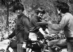 Beatles members John Lennon; George Harrison; and Paul McCartney discuss their lines at the start of a bicycle riding scene for their movie in Nassau, Bahamas on Feb. 24, 1965. (AP Photo)
