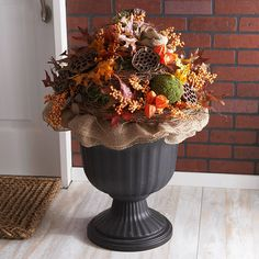 DECORATIVE FALL URN. Build a mound of cut plastic florist's foam pieces inside a plastic urn. Cover with Spanish moss (available at crafts stores), keeping the moss in place with green pins. Make a collar of burlap around the urn and build your arrangement with artificial leaves, berries, Chinese lanterns, dried lotus pods, and other fall favorites from the floral selection of your local crafts store. Green pins help keep everything in place.